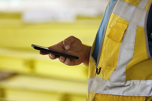 Construction worker using handheld device